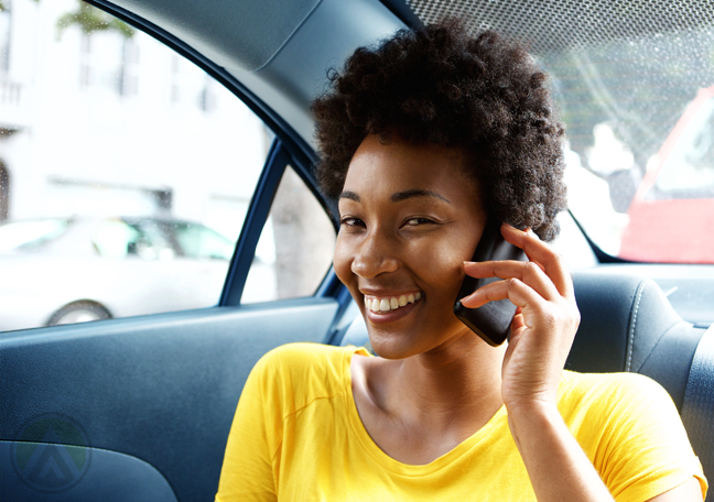smiling woman using phone in car backseat