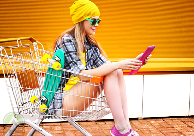 woman in colorful clothes using tablet sitting in shopping cart