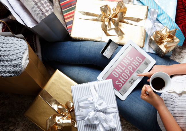 woman sitting on floor with coffee online shopping on tablet surrounded by wrapped gifts