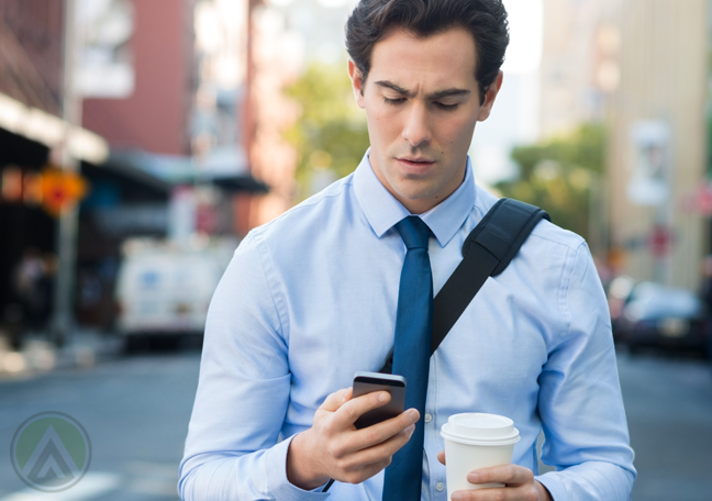 businessman walking street holding cup looking smartphone