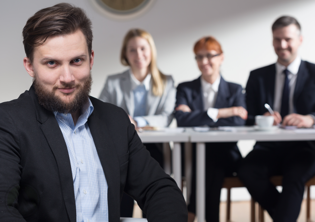 confident job applicant sitting with job interview panel in back