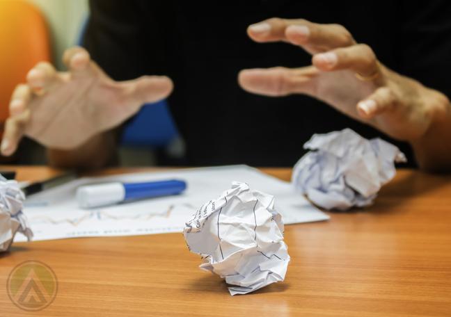 employee hands grab crumpled paper
