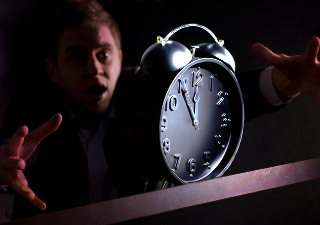 office employee catching alarm clock in dark