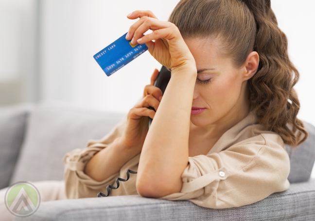 problematic woman holding credit card making phone call