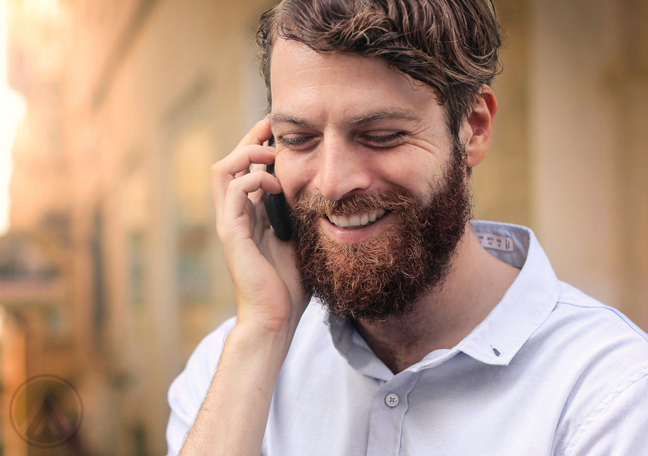 smiling bearded man in phone call