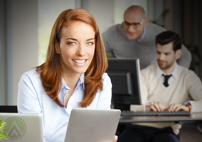 smiling female employee using tablet with coworkers in background