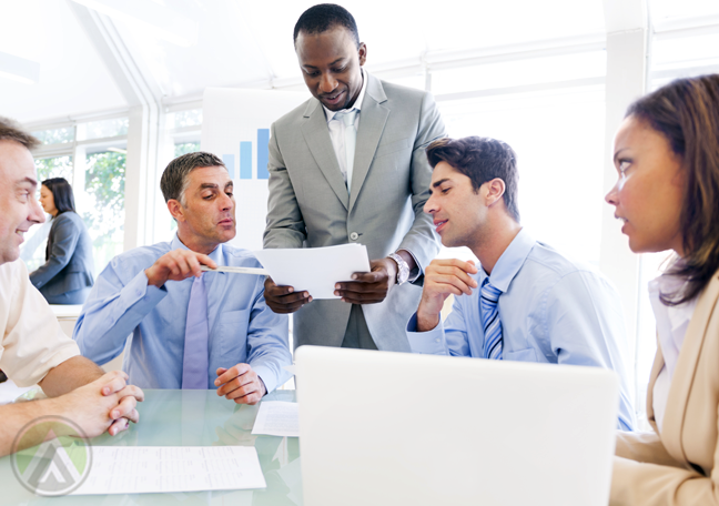 business team in meeting looking printed document