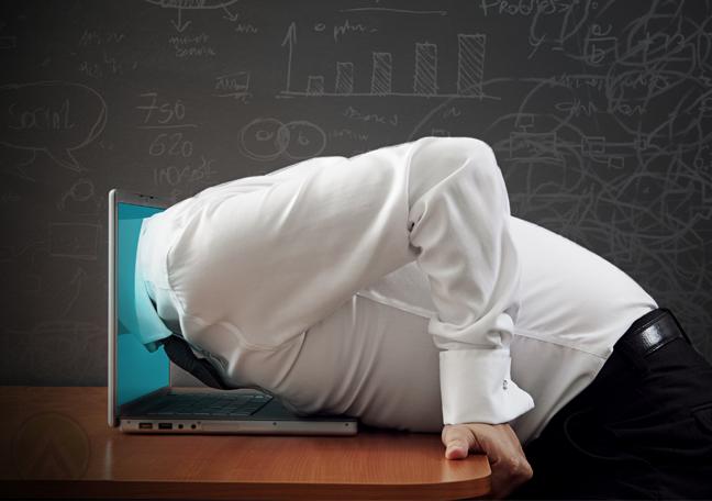 businessman head stuck in laptop screen