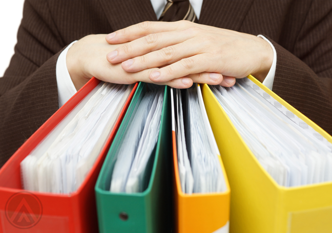 businesssman holding colorful binders of printed documents