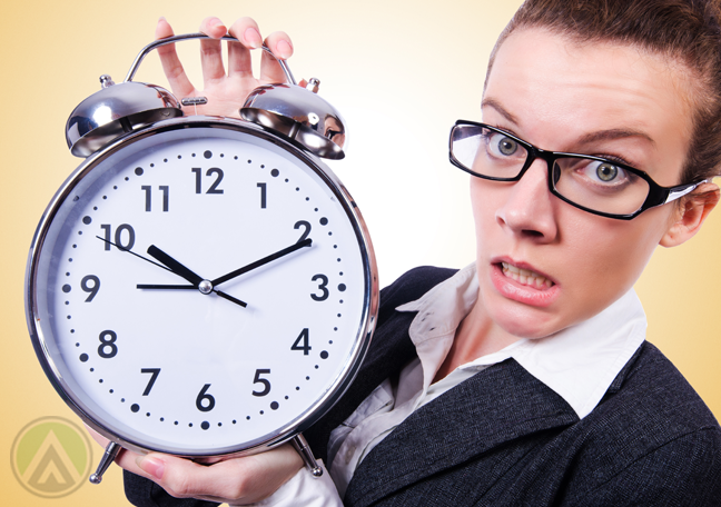 concerned woman in glasses holding giant alarm clock