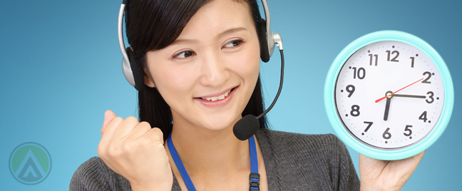 excited asian call center worker holding wall clock