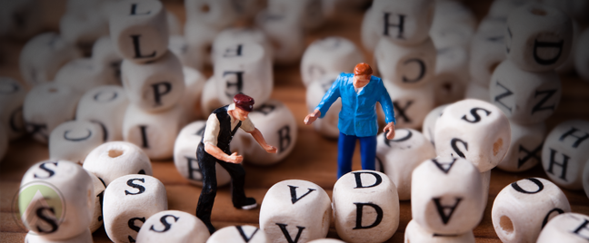 miniature business figures standing in middle of boggle blocks