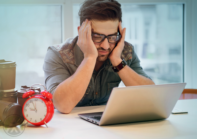 office worker with headache using laptop with red alarm clock coffee cups