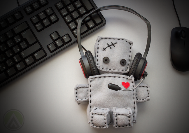 rag doll with headphones on computer table with keyboard mouse