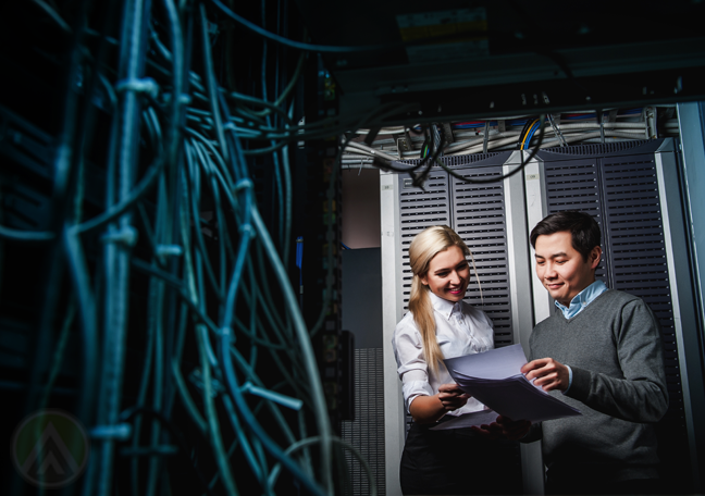 Asian IT manager with system administrator looking at printed reports by IT server room