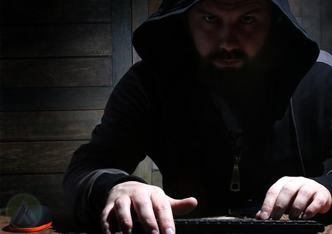 bearded hacker wearing hoodie in dark using computer