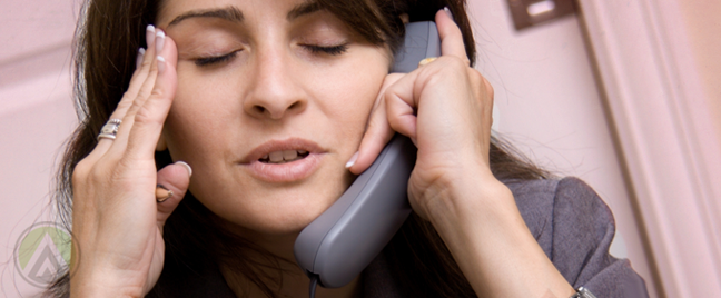 business woman with headache talking on phone