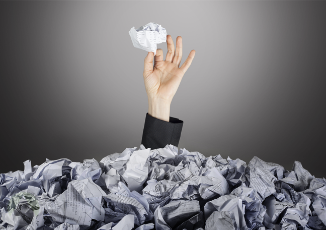 businessman buried in crumpled paper holding up paper