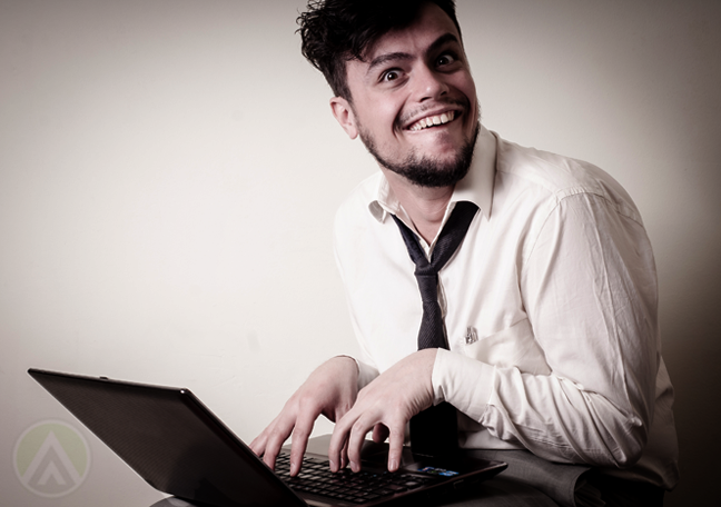 businessman using laptop with nasty grin