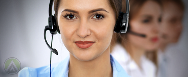 close up female call center rep with customer service team in back