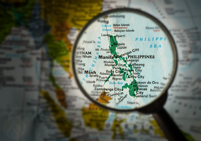 magnifying lens pointing to Philippines on map