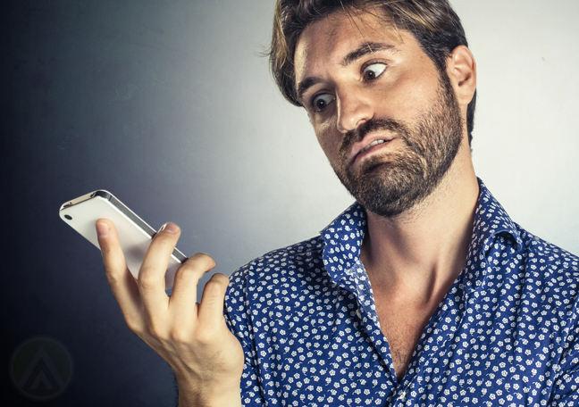 man in hawaiian blue shirt annoyed at phone