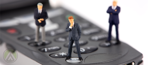 miniature figures business men standing on flip phone keypad