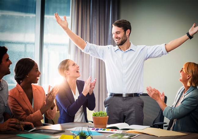 proud office employee arms outstretched applauded by coworkers