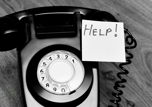 rotary landline telephone with post it note with help written