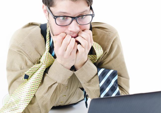 shocked businessman dishelved looking at laptop screen