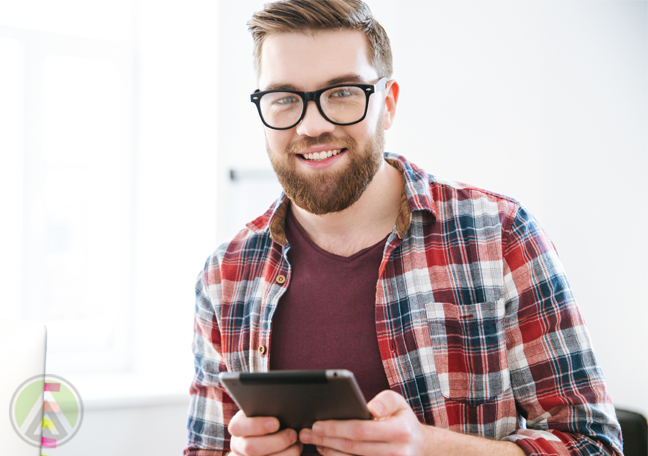 smiling bearded office worker holding tablet computer