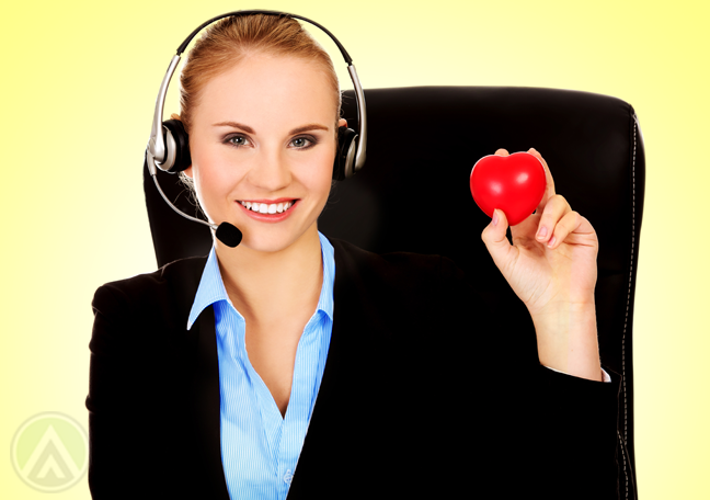 smiling blond call center agent holding rubber heart