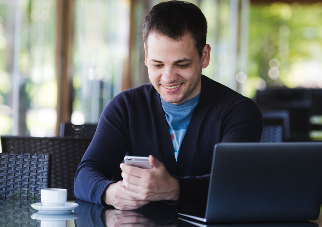 smiling man having coffee texting in cafe using laptop
