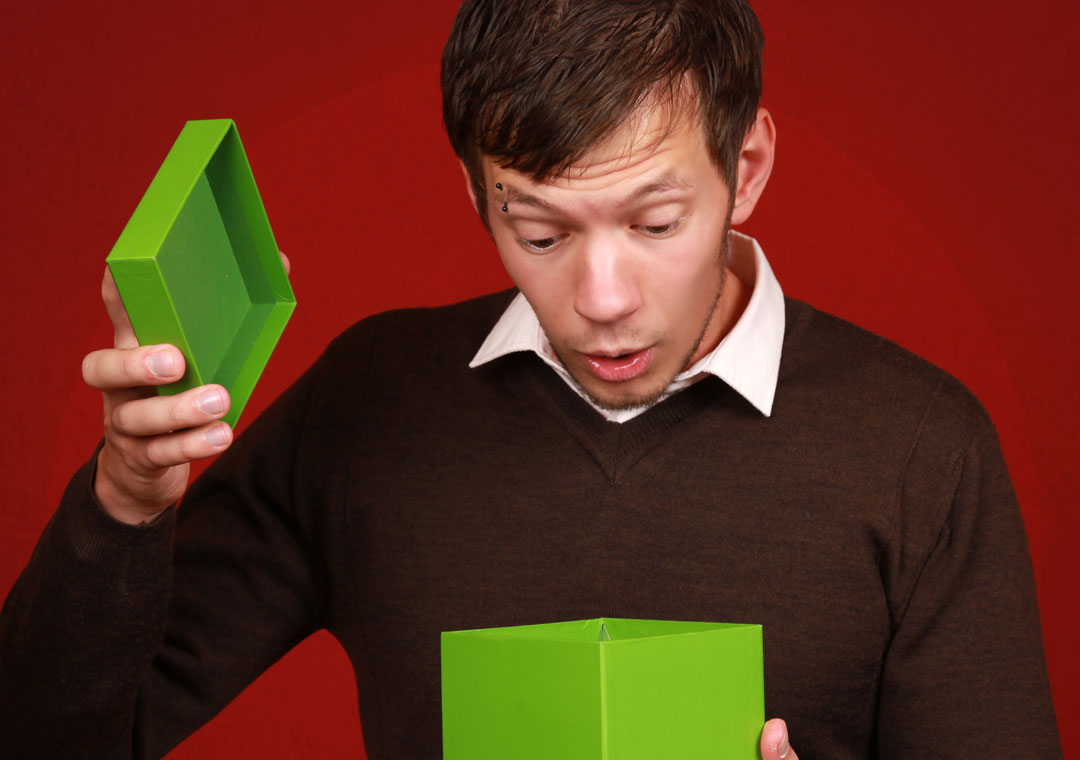 surprised young man looking into opened box gift