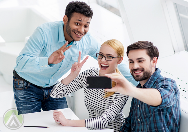 young business coworkers taking selfie in office