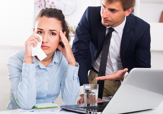 boss reprimand crying employee using laptop
