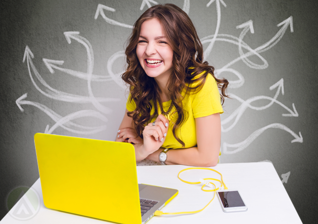 smiling woman in yellow using laptop
