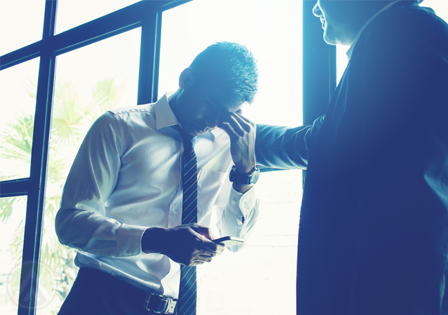 businessman consoling sad business partner holding smartphone standing by window