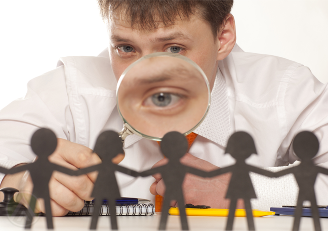 businessman looking at paper people through magnifying lens
