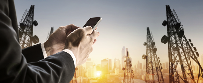 businessman using smartphone outdoors view of communciations cell towers