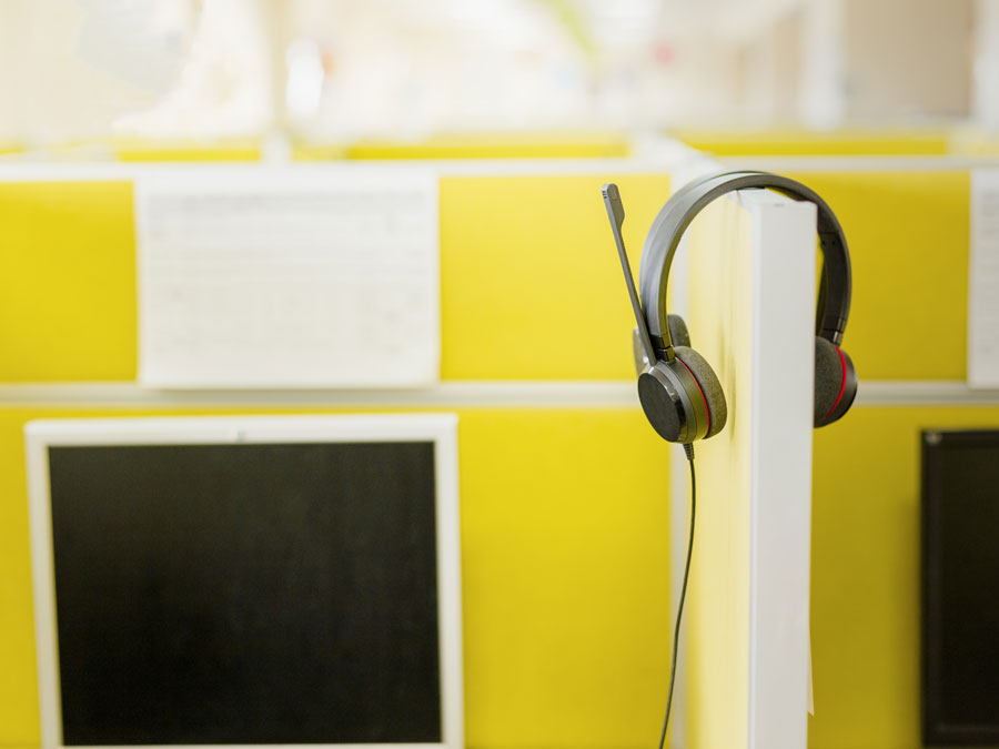 call center headphones haniging on yellow table divider