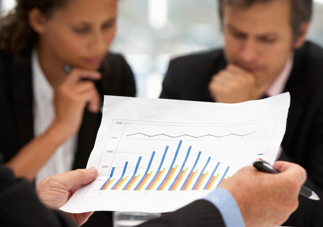 close up printed business document charts graphs in background executives in a meeting