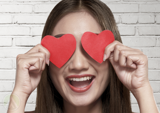 delighted woman holding paper hearts to eyes