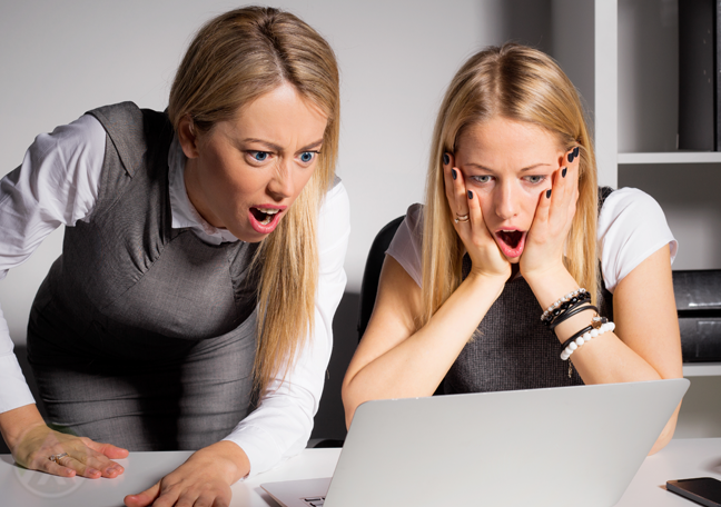 disgusted shocked office women looking at laptop