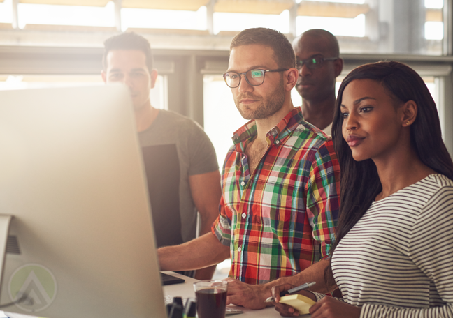 diverse business team looking at presentation on large computer monitor