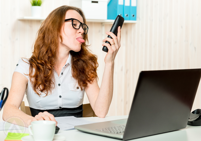 female office employee in glasses using laptop sticking tongue out at smartphone
