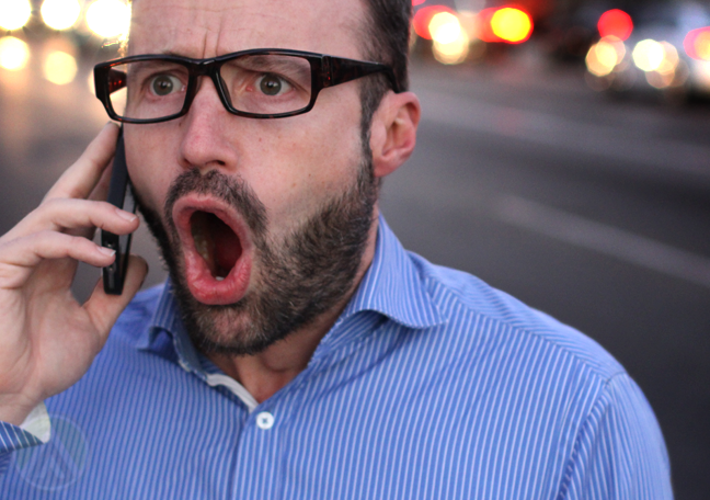 frustrated man in glasses shouting into smartphone