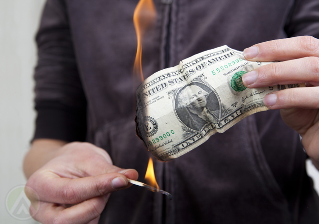 hand using match to burn money