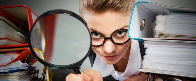 office employee in glasses using large magnifying lens between stacks reports