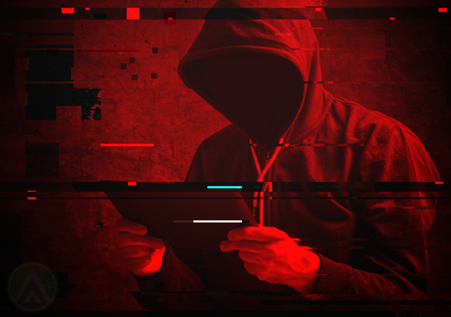 red photo of cybercriminal in hoodie holding tablet
